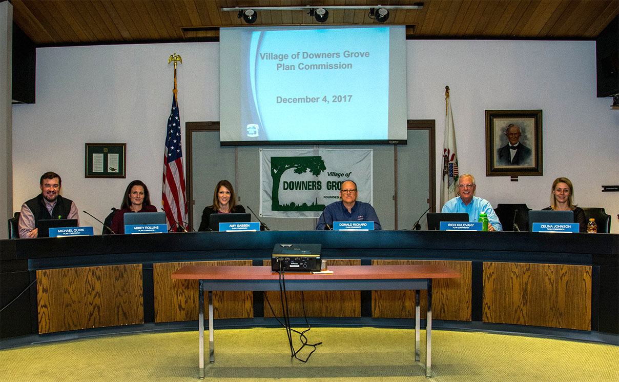 Picture shows six seated members of the Plan Commission in the Village Hall Council Chambers.