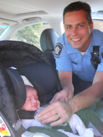 Officer Chris Fisher makes sure Baby Reese is properly restrained in her car seat.
